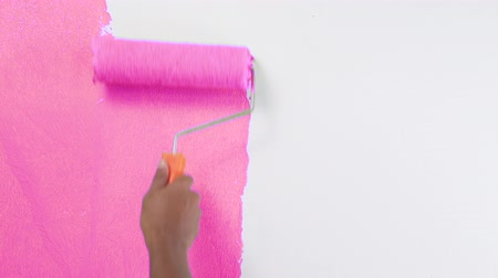 pára choque : Footage hand painting a white wall from scratch with a pink paint roller