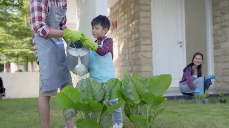 outdoor hobby : father and son watering a plant in front of their house together