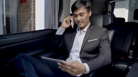 move well : businessman calling by phone and using tablet in the car Stock Footage
