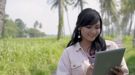 asian woman using tablet pc under coconut trees Wideo