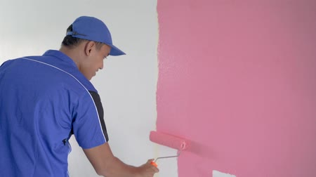 young worker painting on the wall
