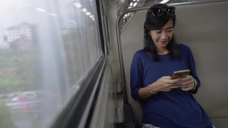 assentos : asian young woman hold smartphone alone when take the train go to town Stock Footage