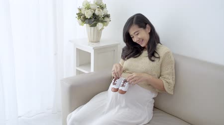 estomac : Pregnant woman holding baby shoes Vidéos Libres De Droits