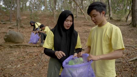 coletando : young volunteers cleaning plastic trash rubbish from park