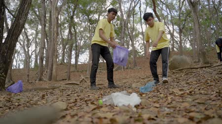 coletando : two young man volunteers cleaning rubbish