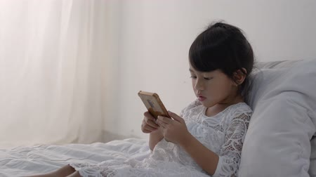 невинный : kid lying on bed wearing white using mobile phone