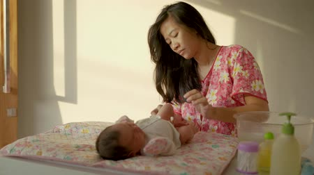 replace : Asian little baby girl diaper replaced with a mother Stock Footage