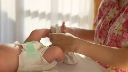 replace : mother changing clothes of her newborn baby at home Stock Footage