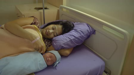 newborn child : Newborn baby laying in crib with his mother lying on bed side