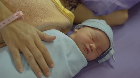 newborn baby : Newborn baby laying in crib with his mother lying on bed side