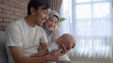 playful infant : muslim parent kissing together with baby boy Stock Footage