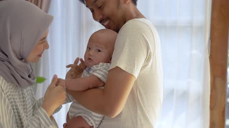 joyfulness : muslim parent kissing together with baby boy Stock Footage