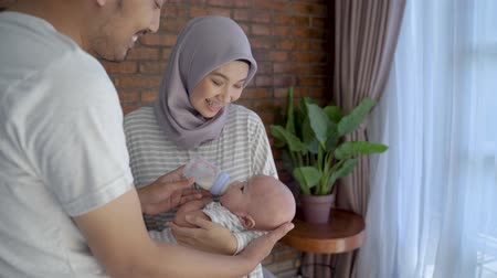 infant formula : parent feeding baby with bottle of milk