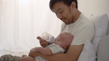 infant formula : father giving a bottle of milk to his newborn baby