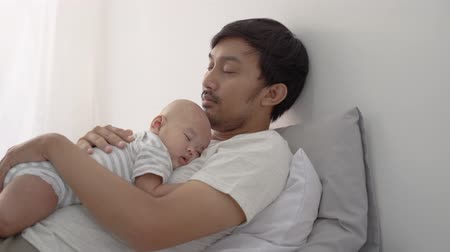 sonolento : infant asian newborn baby sleeping on his fathers chest