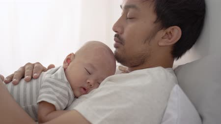 beijos : infant asian newborn baby sleeping on his fathers chest
