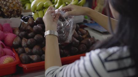 bakkal : pregnant asian woman choose snake fruits the items purchased
