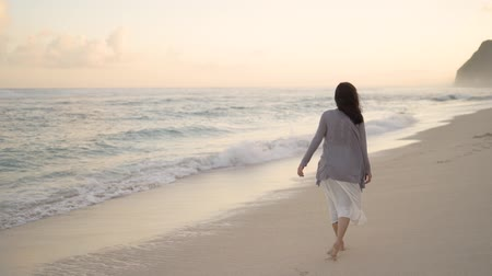 bronzeada : woman walking on white soft sand beach