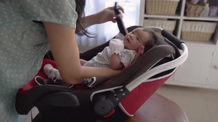 se coucher : Asian mother putting baby into seat