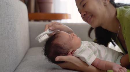 babycare : asian mother hold and combing little daughter hair