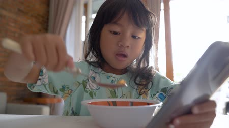 distraido : distracted kid using mobile phone while having breakfast Archivo de Video