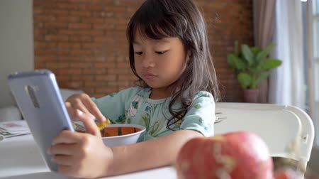 eat : distracted kid using mobile phone while having breakfast Stock Footage