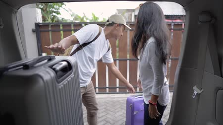 coisas : couple put suitcases in to the car trunk