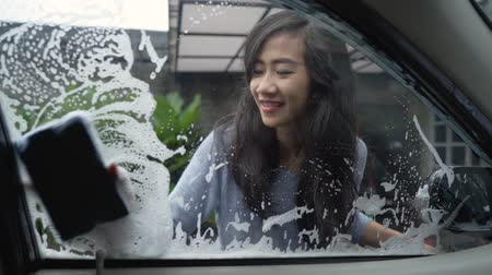esfregar : woman wash her car window with soap