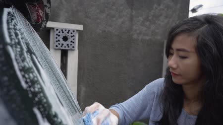 garagem : asian woman washing her car
