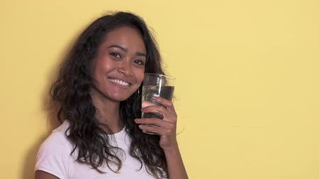 дубленый : pretty asian girl holding a glass of mineral water Стоковые видеозаписи