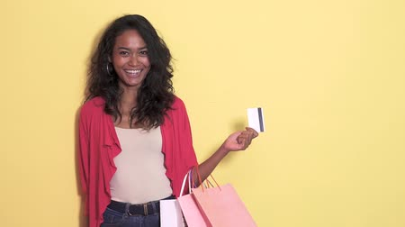 tarjeta amarilla : casual asian woman with shopping bag holding a credit card Archivo de Video