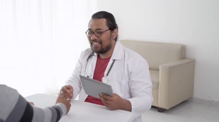 tab : smiling doctor shaking hand with patient in his office
