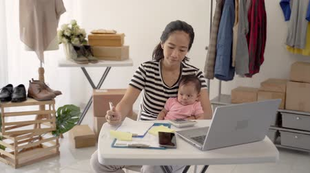 retailer : woman with baby working from home of her online ecommerce shop Stock Footage