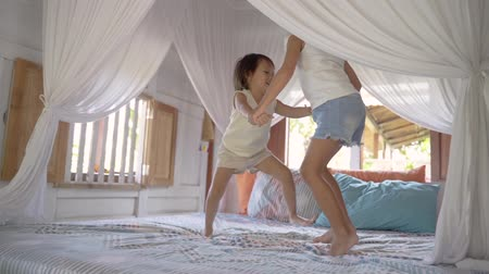 pré escolar : Asian little girls playing on bed together Stock Footage