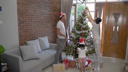 natal : family and daughter hanging decorating christmas tree Stock Footage