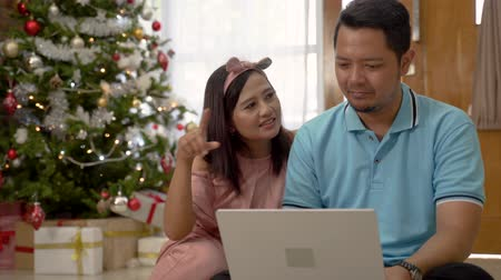 sitting floor : asian couple using laptop on christmas day