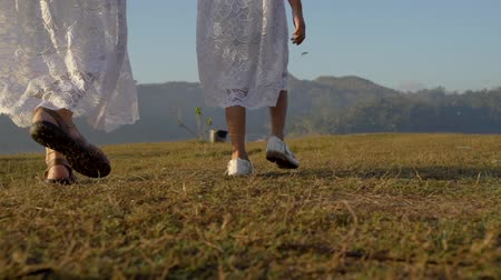 gramíneo : asian mother and daughters legs walk on the grassy yard