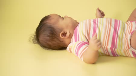 младенчество : baby laying on yellow background Стоковые видеозаписи