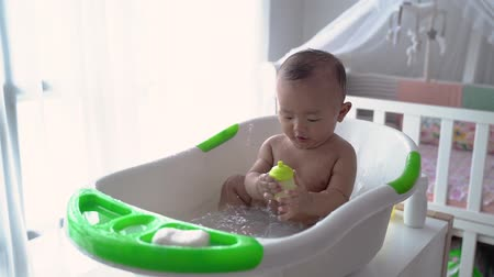 boy toddler enjoy play with water while taking a bath