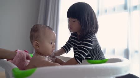 helpful sister wash her baby brother during bath time Vídeos