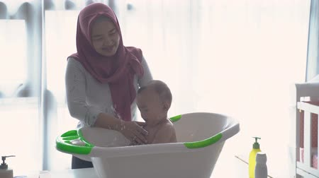 muslim asian woman wash her baby in the basin Стоковые видеозаписи