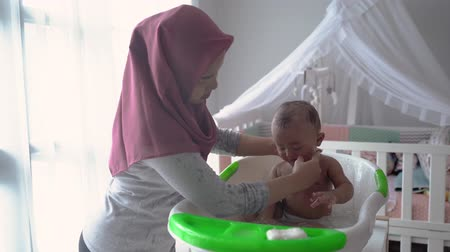 muslim Mother washing little boy in bathtub