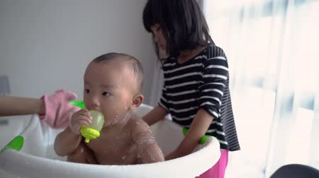 sister help her mother to wash baby brother