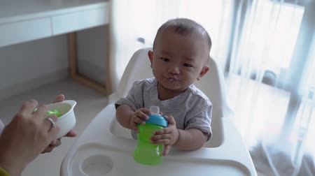 asian child eating solid food from mother Стоковые видеозаписи