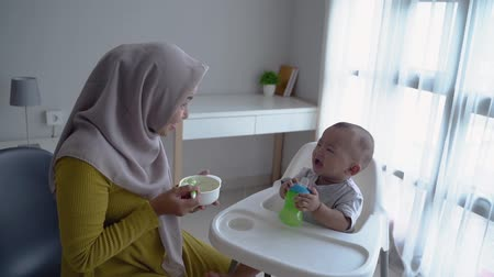mother feeding her baby boy while sitting on high chair Vídeos
