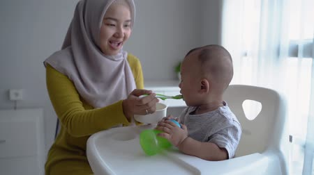asian Mother feeding her baby son with spoon Stockvideo