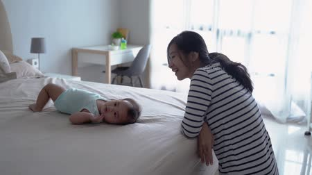 milestone : mother motivate her baby to roll over Stock Footage
