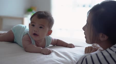 milestone : mother playing with her baby on the bed Stock Footage