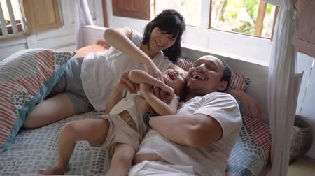 Asian happy family and child daughter relaxing on the bed
