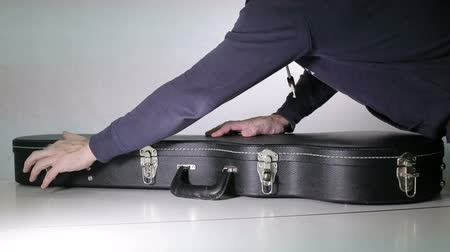 защелка : A man opens a case and takes a guitar out of a case. Стоковые видеозаписи